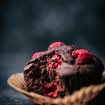 Chocolate raspberry muffin, close up in a paper liner, with a bite taken out to show interior texture.