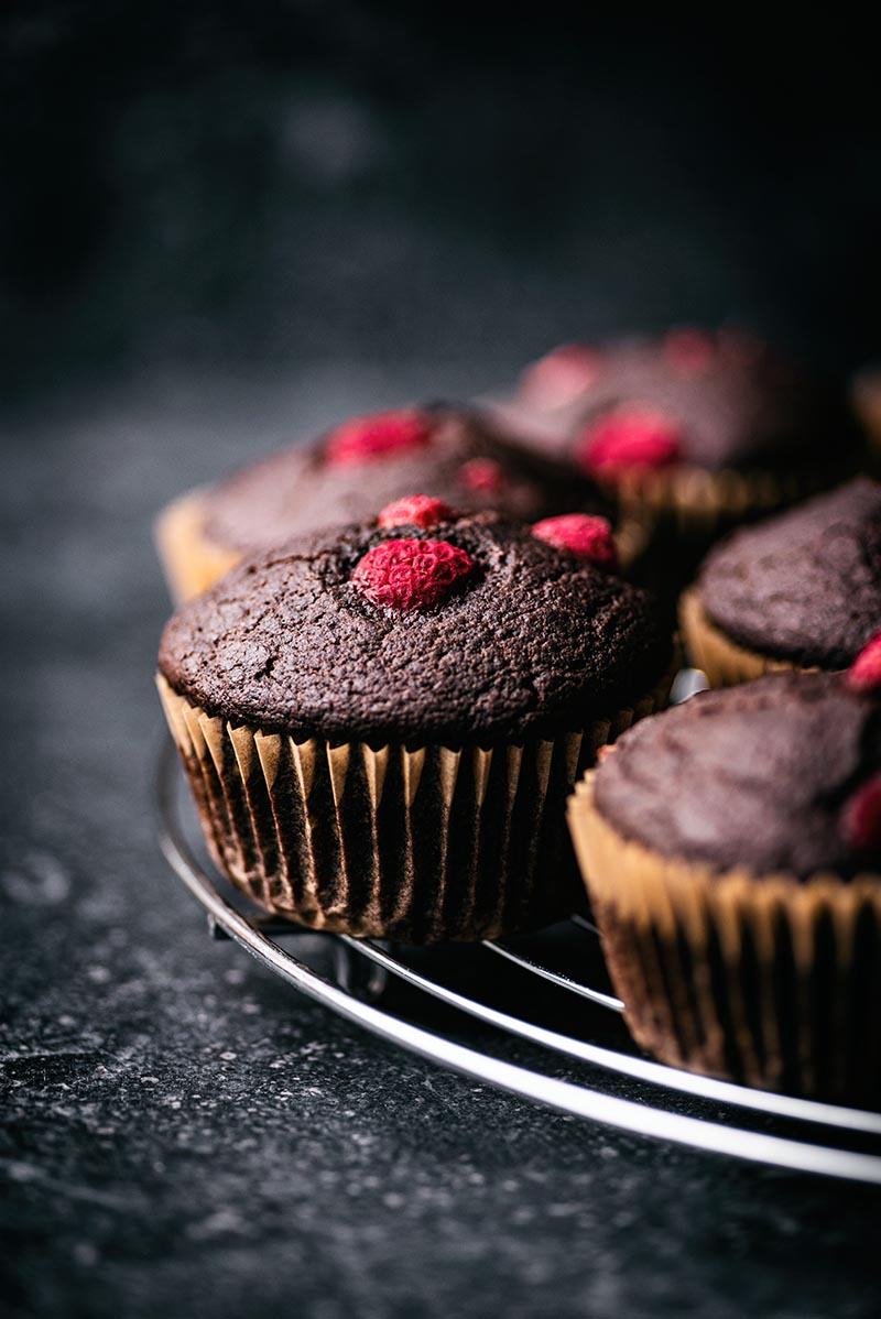 Raspberry chocolate muffins on a cooling rack.