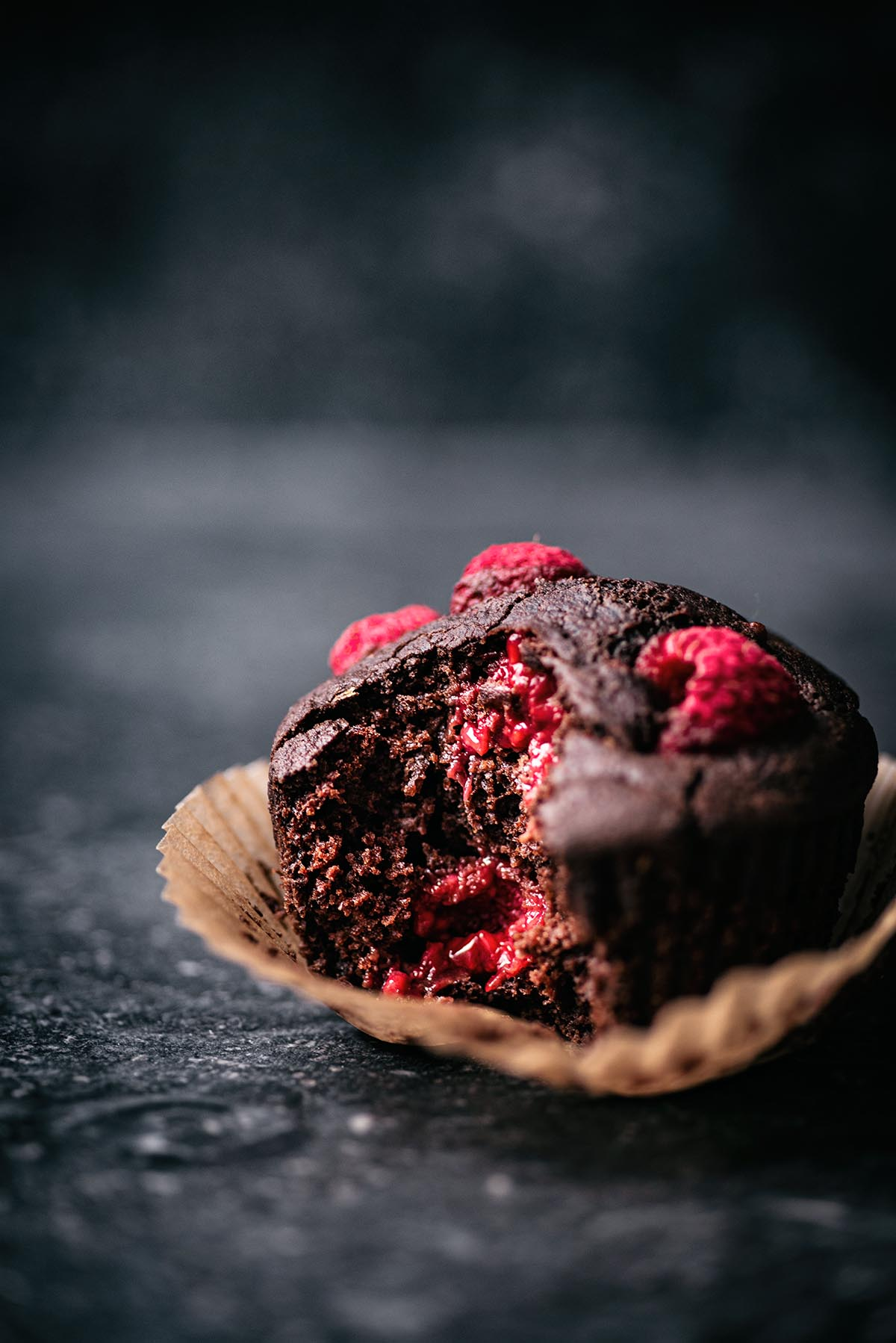 Chocolate raspberry muffin with a bite taken out to show interior texture.