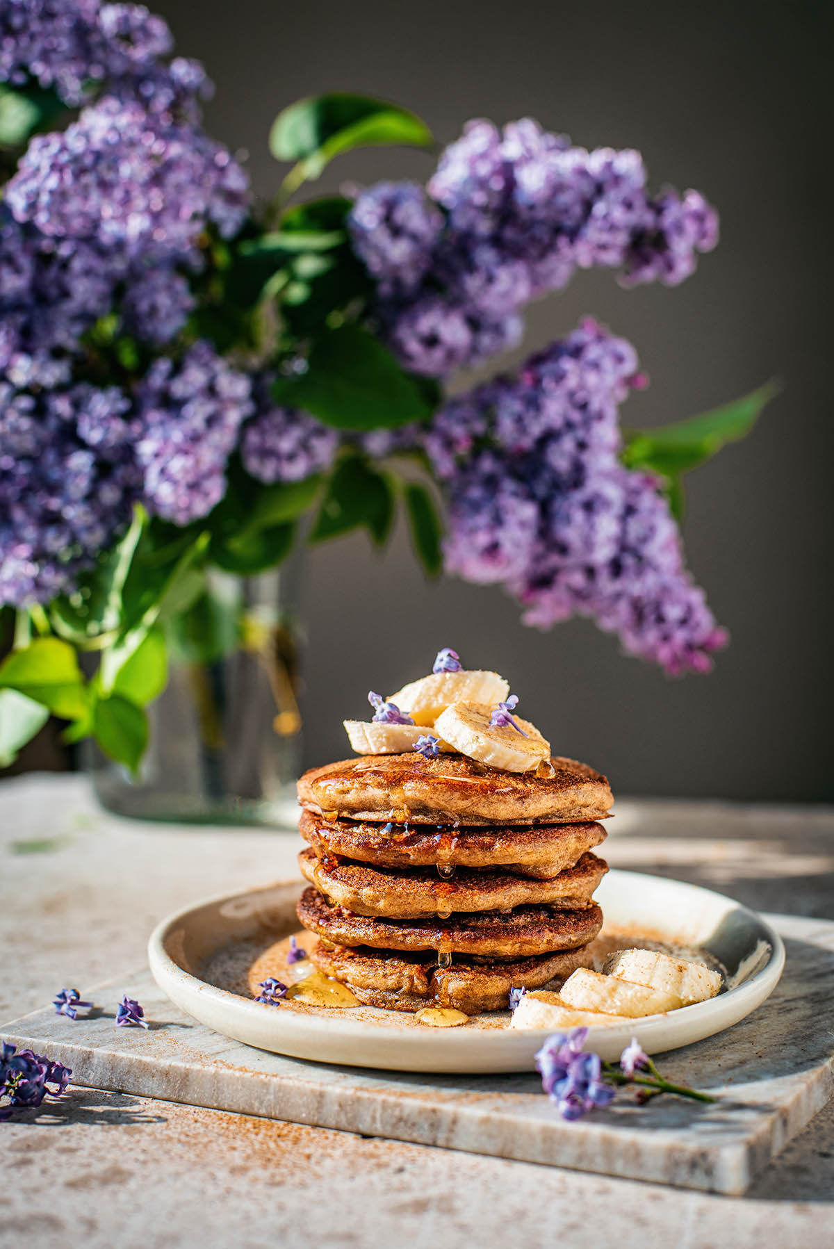 Stack of pancakes topped with bananas and lilac blossoms.