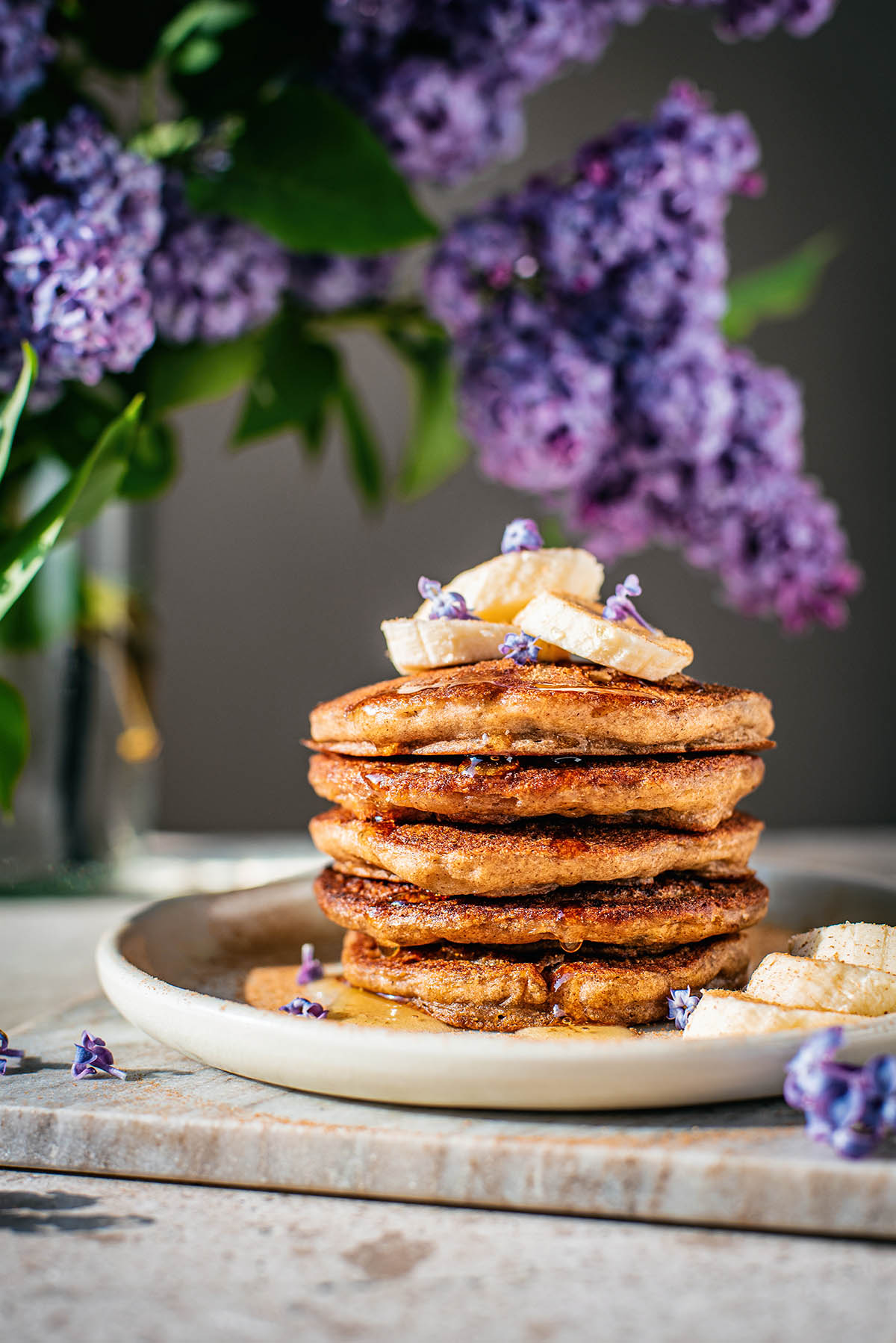 Stack of gluten free banana pancakes topped with bananas and lilac blossoms.