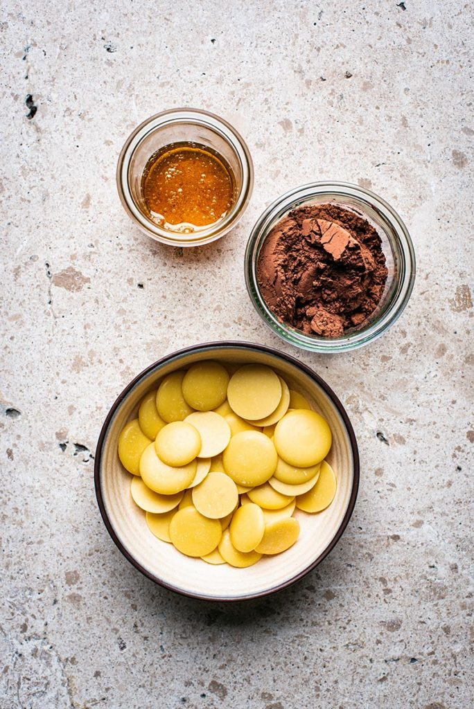 Three dishes, top down view. Jar with honey, jar with cacao powder, and small bowl with cacao butter pieces.