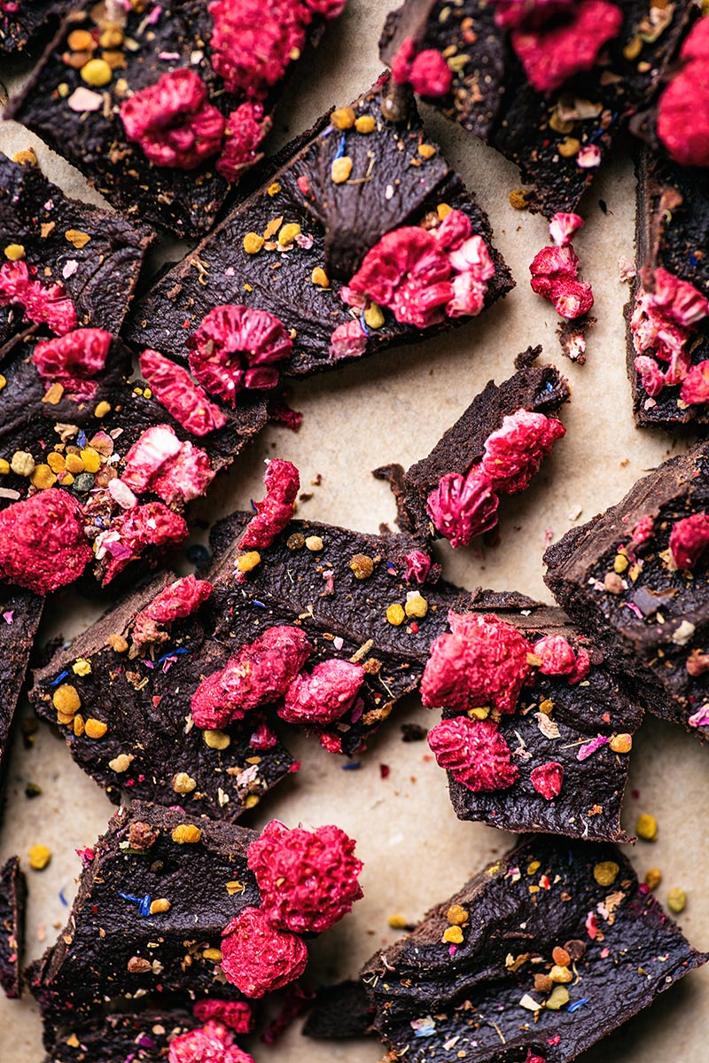 Close up of broken pieces of raw chocolate with dried raspberries, bee pollen, and dried flowers on parchment.