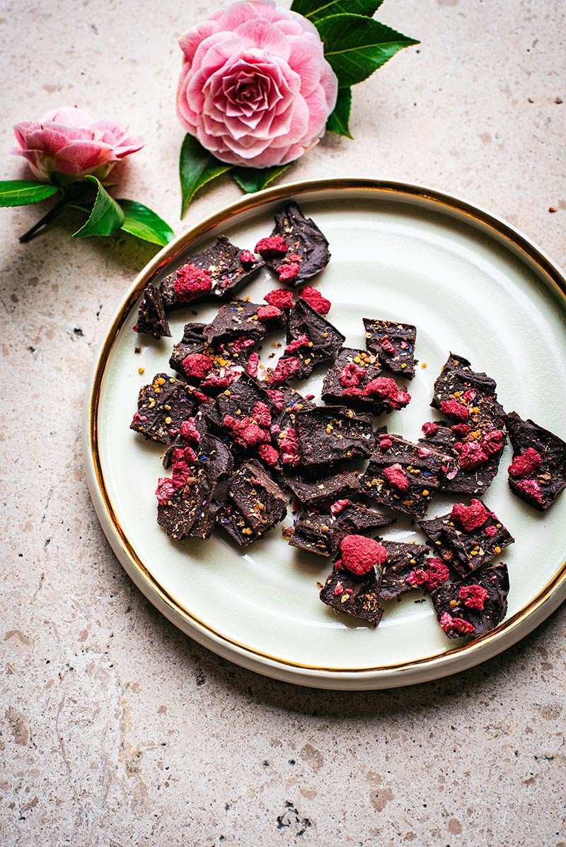 Raw chocolate pieces on a large plate with gold rim and camellia flowers in the background.