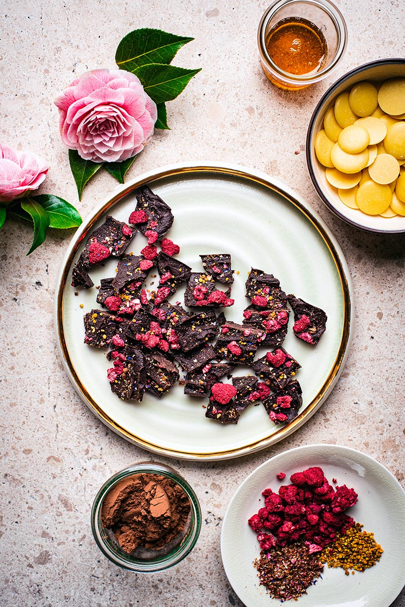 Top down view of chocolate pieces on a large plate surrounded by chocolate ingredients and camellia flowers.