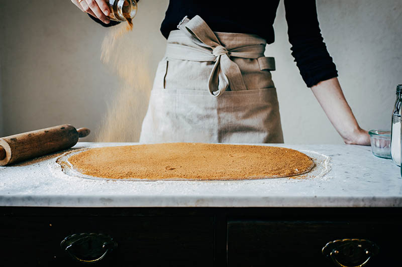 Woman sprinkling cinnamon onto rolled out dough.