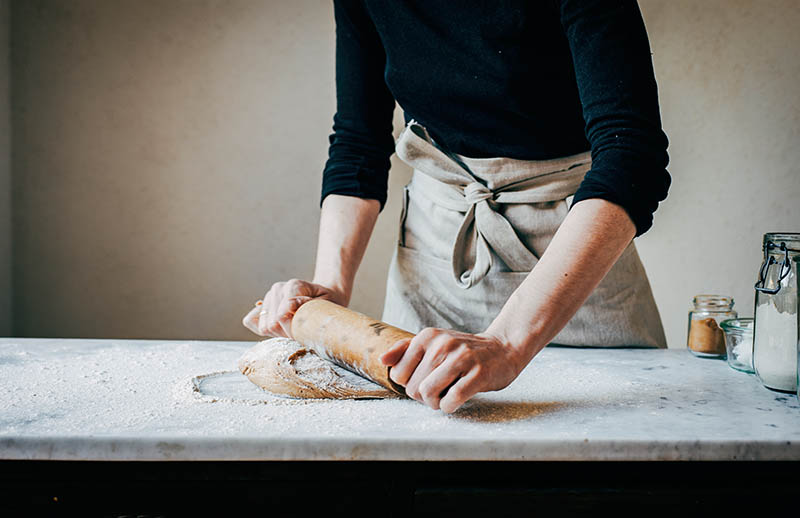 Woman rolling dough on marble surface.
