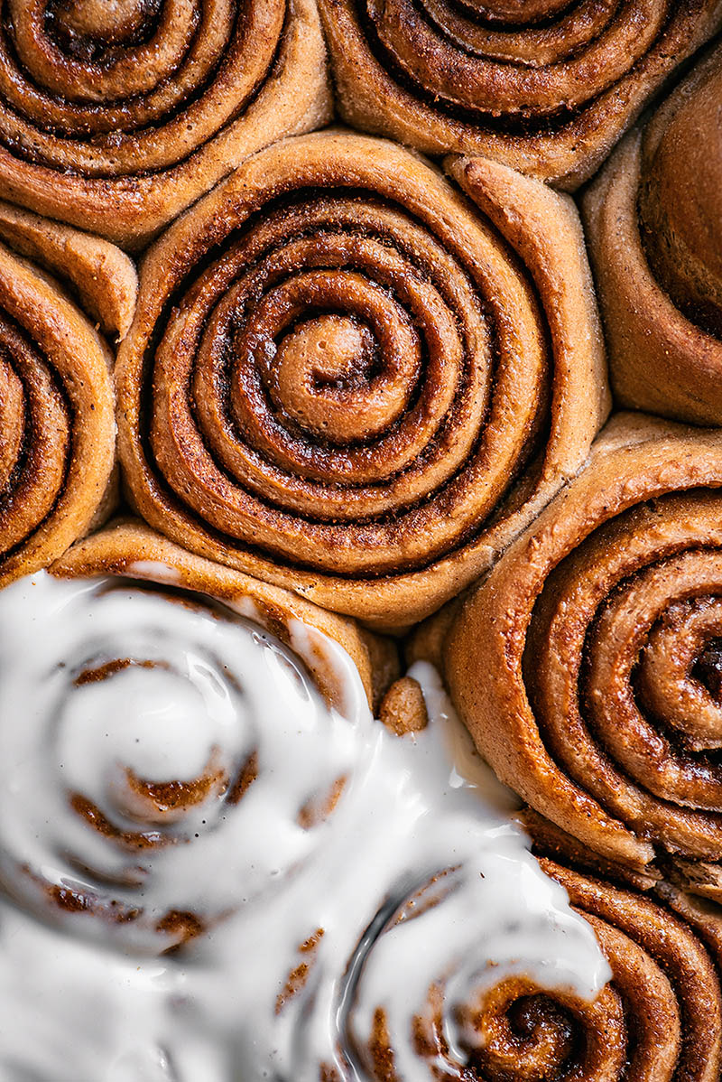 Cinnamon rolls from top down, partly covered in icing.