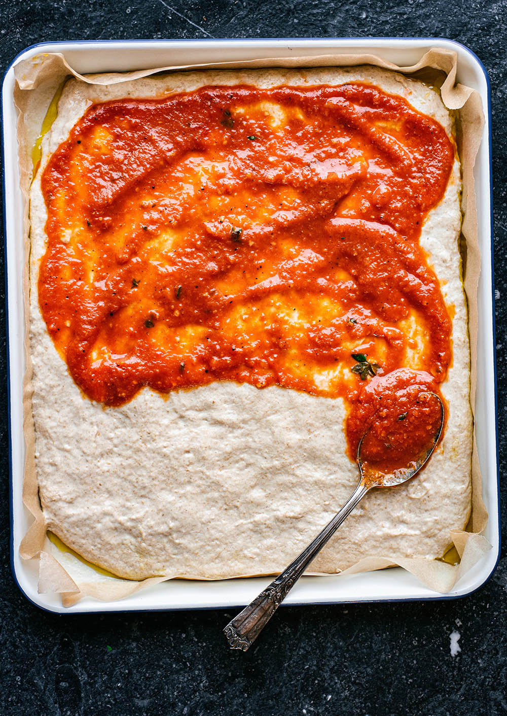 Pizza dough in rectangular dish, half covered in tomato sauce, with spoon.