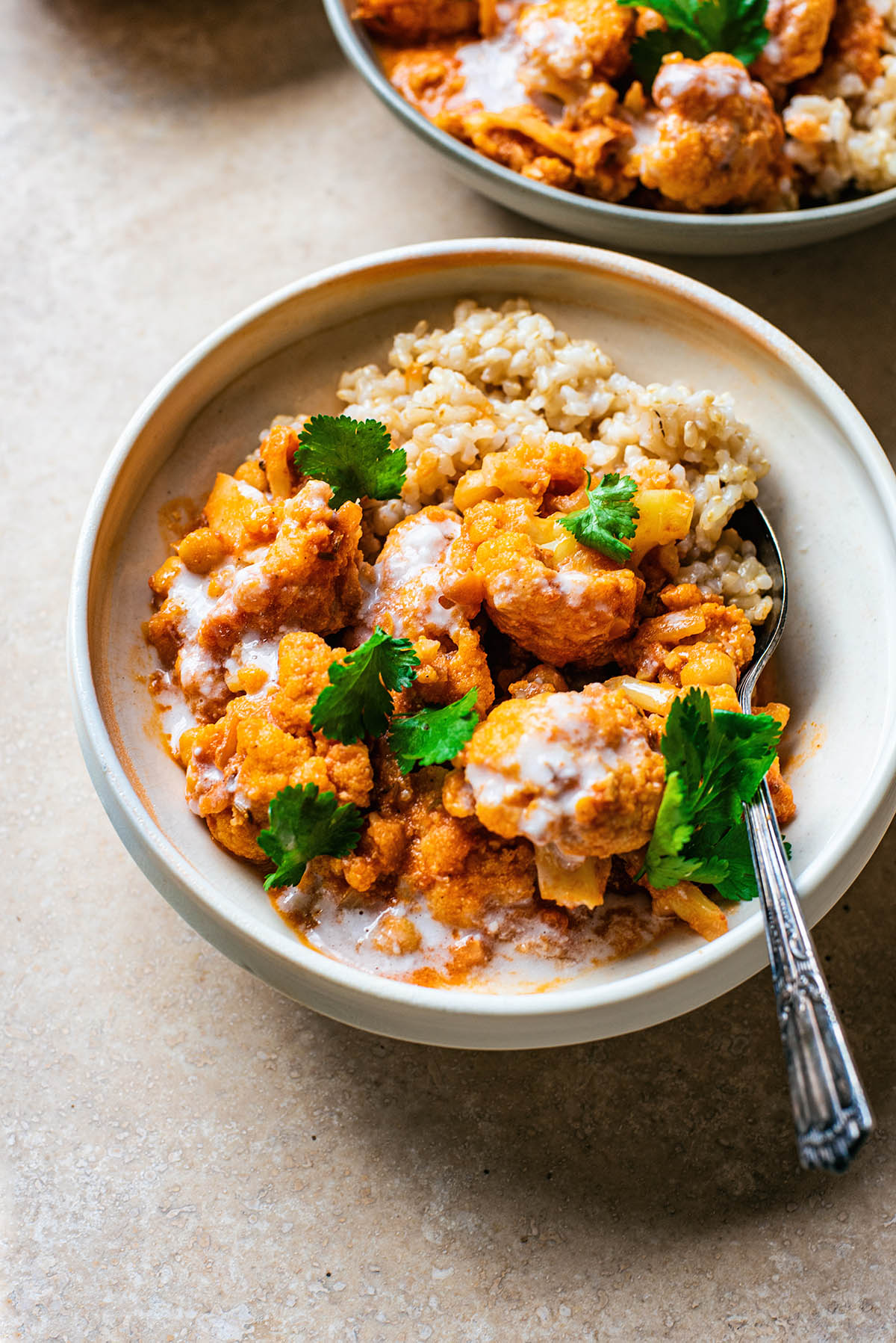 Cauliflower curry in a bowl with cilantro and rice.