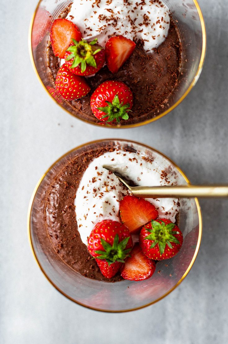 Close up of two cups of chocolate mousse with whipped cream and strawberries.