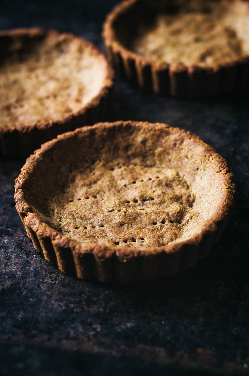 Small tart tins with par-baked tart dough, poked with fork holes.