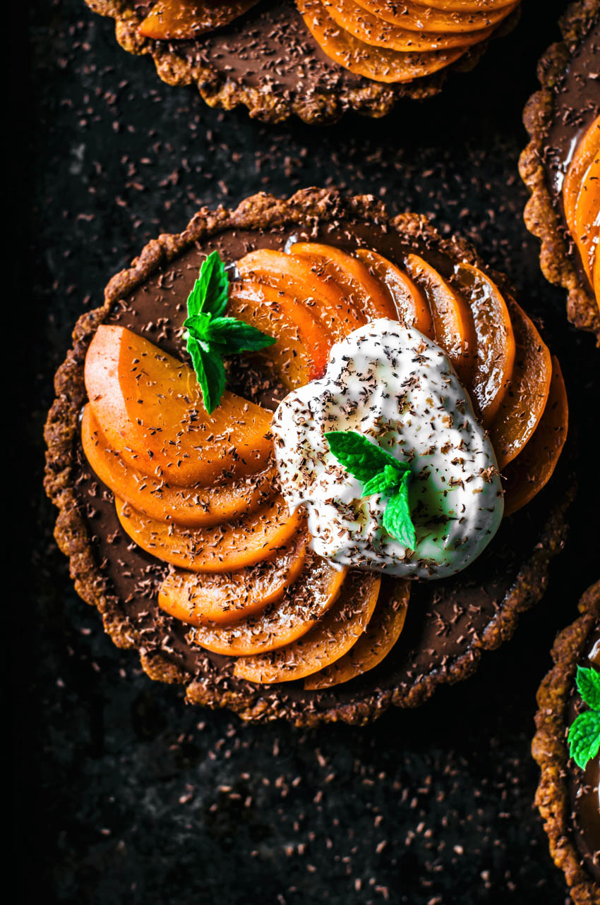 Top down view of four chocolate ganache filled tarts topped with sliced apricots and yogurt.