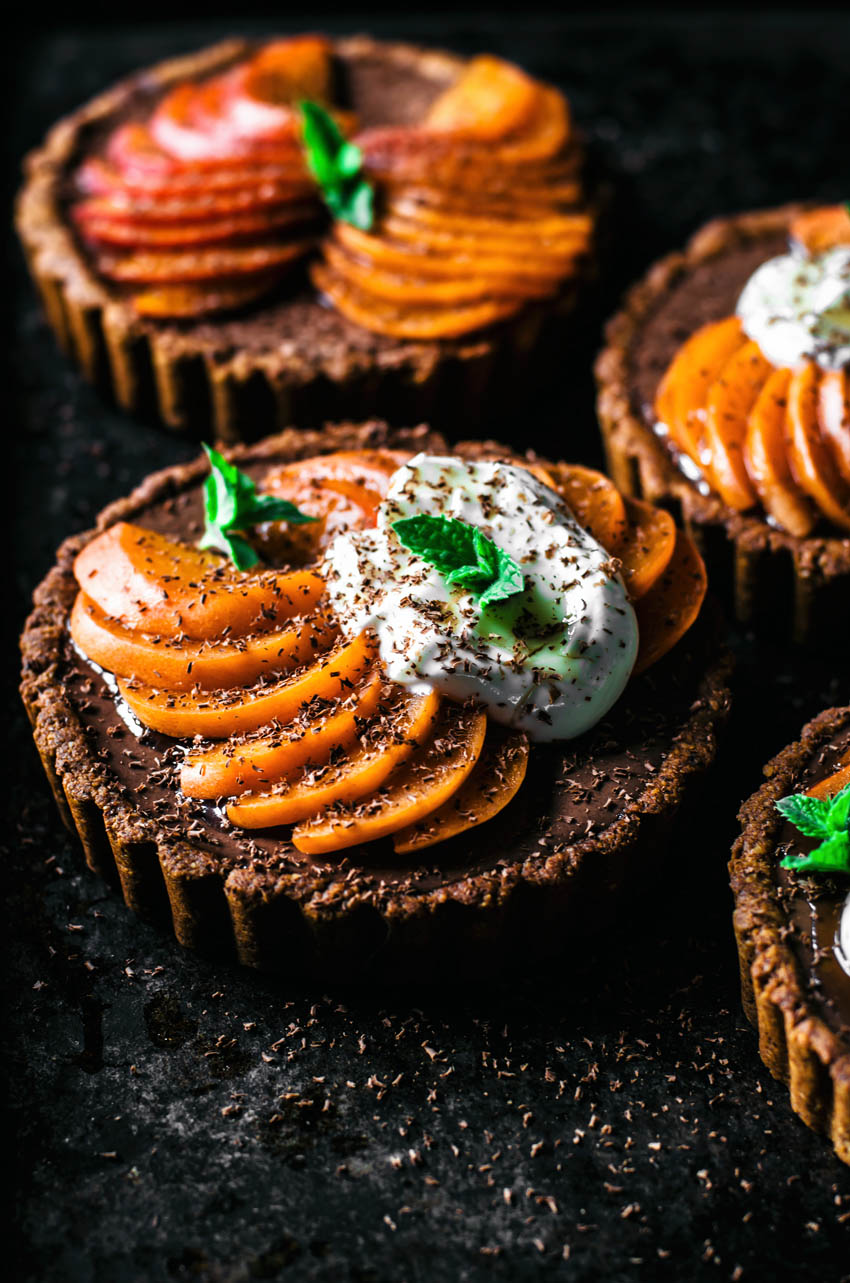 Front view of small tarts with chocolate filling topped with apricot slices.