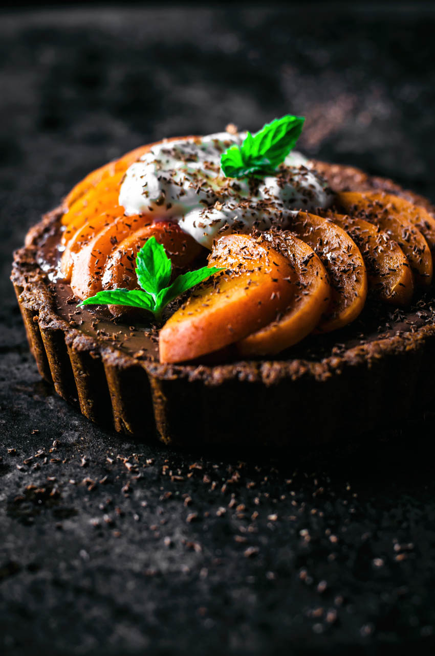 Front view of a tart with chocolate filling topped with apricot slices.