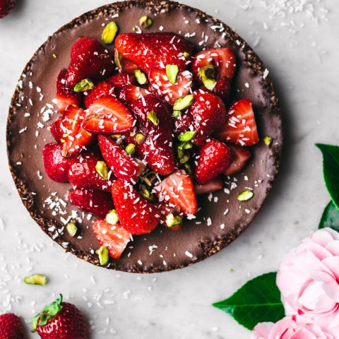 Chocolate coconut pie topped with strawberries and pistachios.