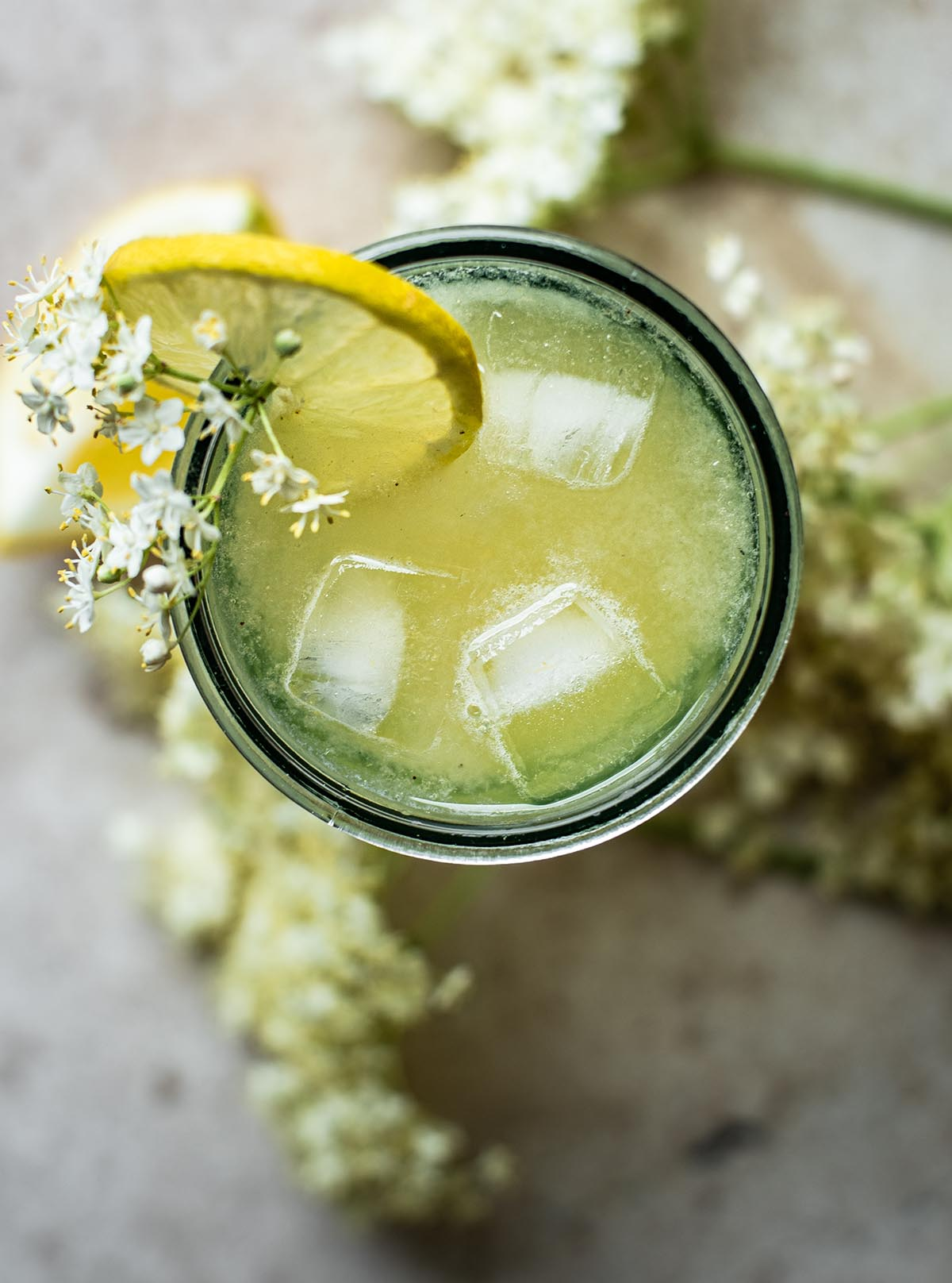 Top down view of elderflower lemonade in a glass with ice.