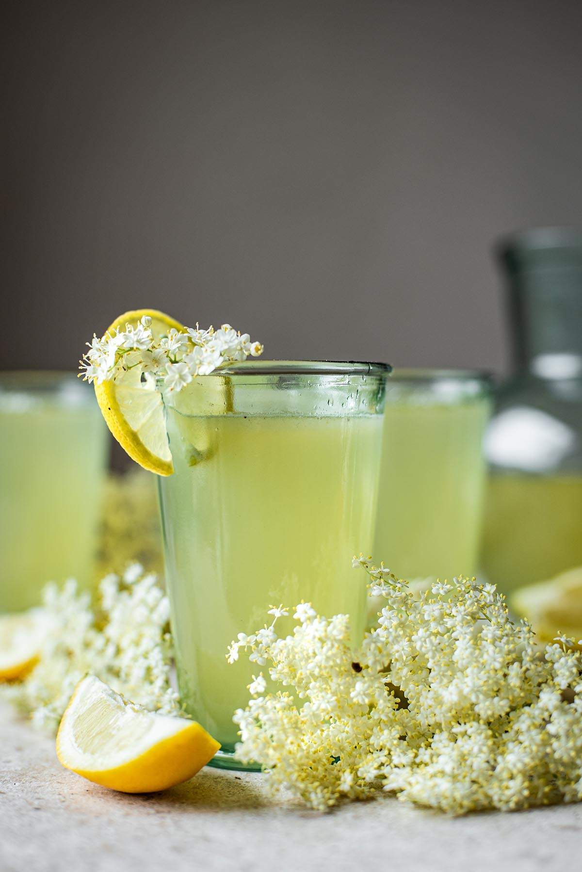 Three glasses of elderflower lemonade with a pitcher in background.