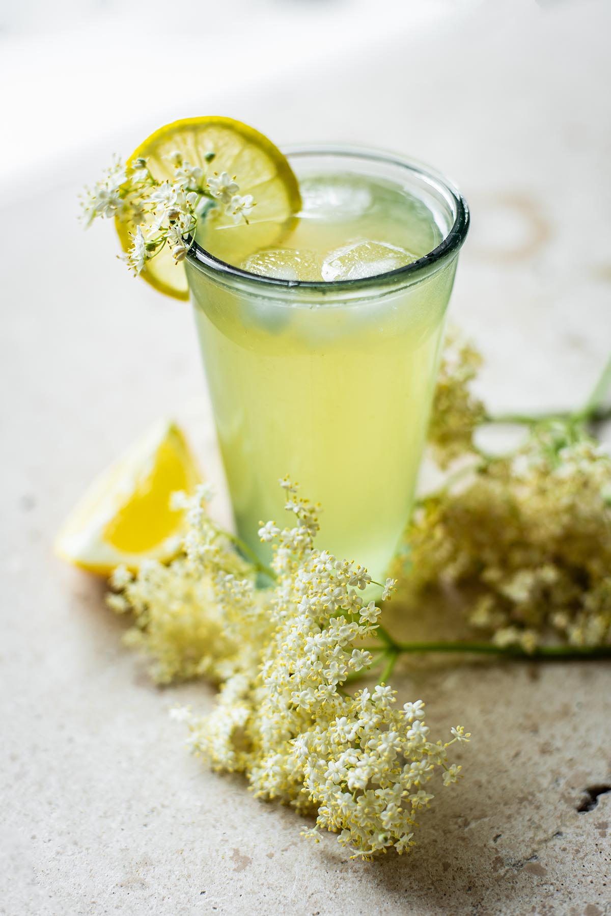 A glass of lemonade with elderflower and ice.