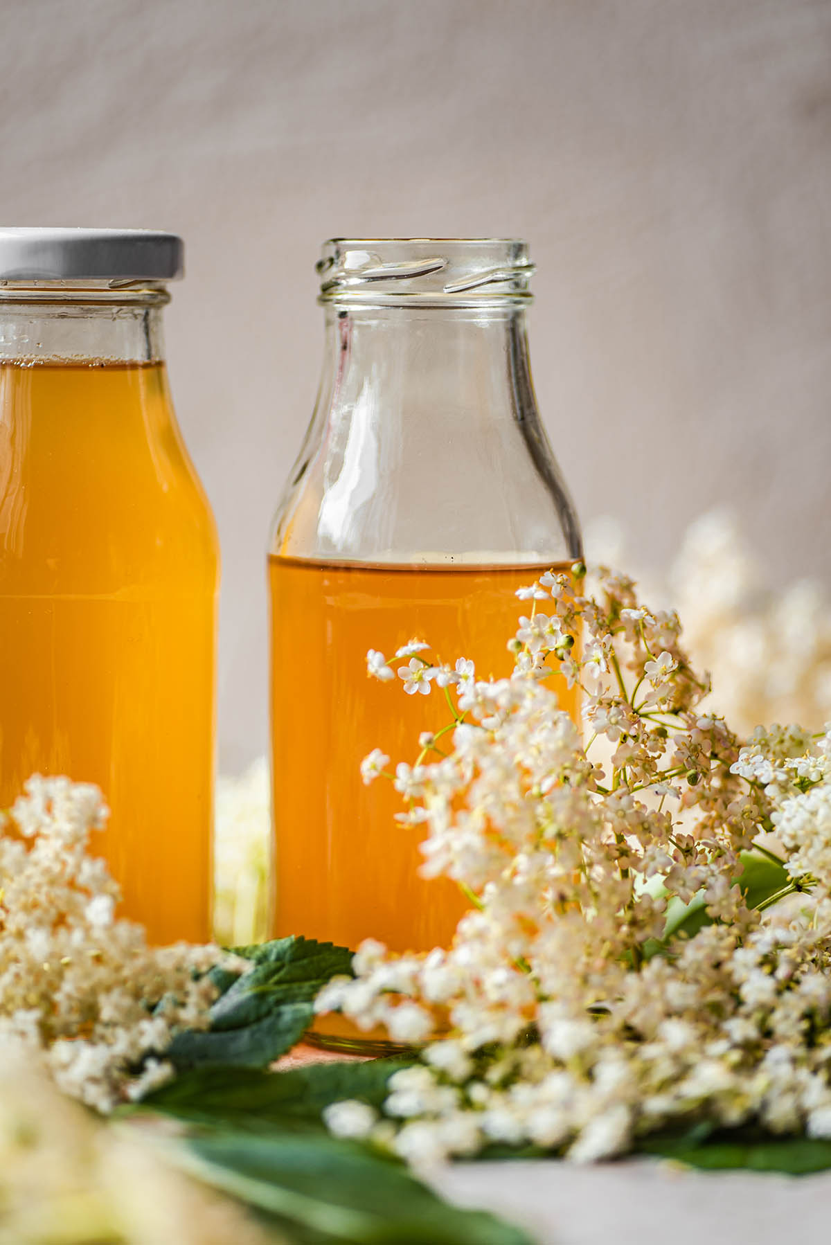 Two small glass bottles filled with elderflower cordial.