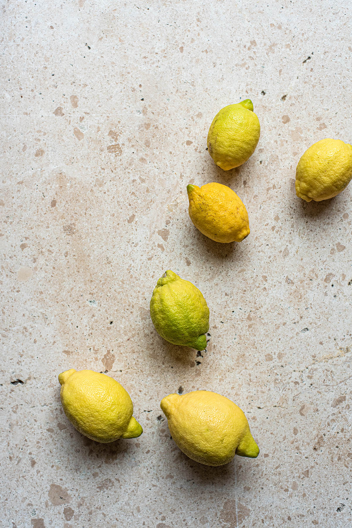 Six lemons, greenish yellow, on a stone surface.