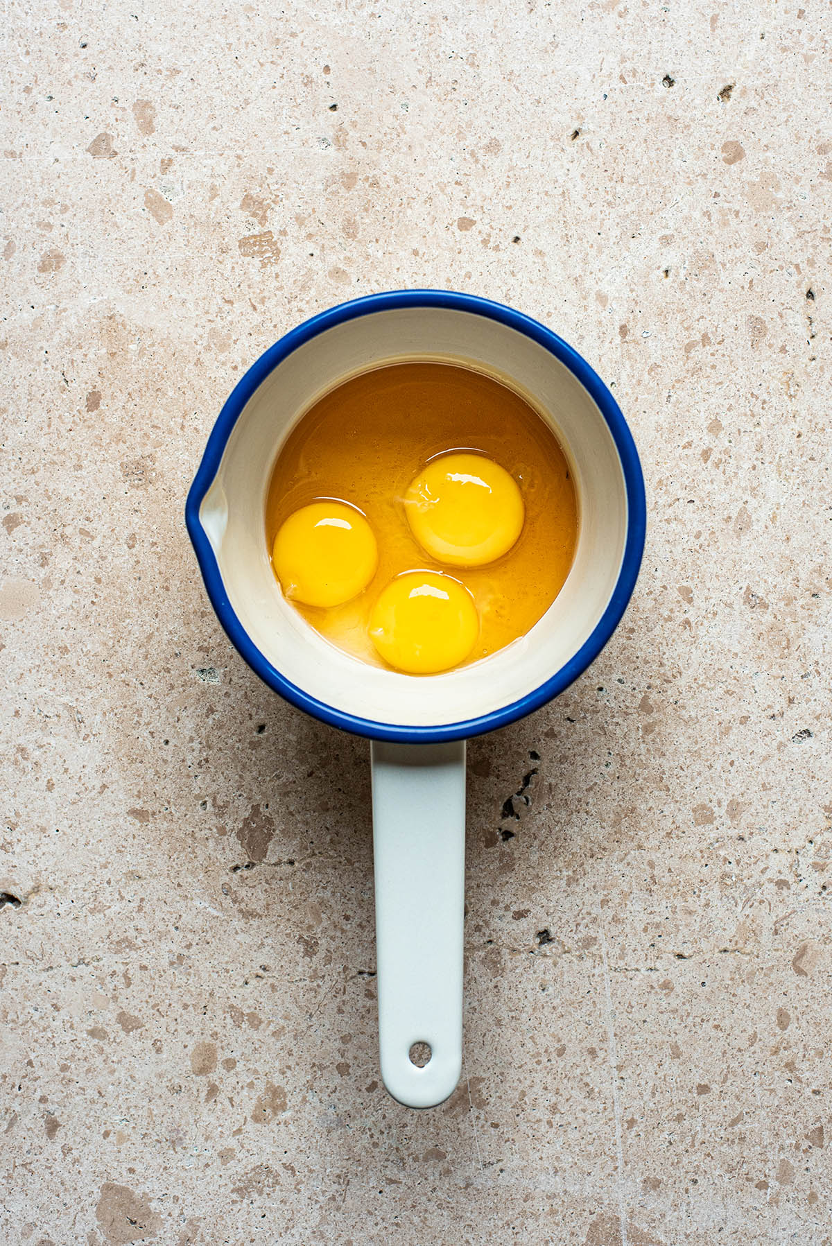 Three egg yolks in a small saucepan with honey.