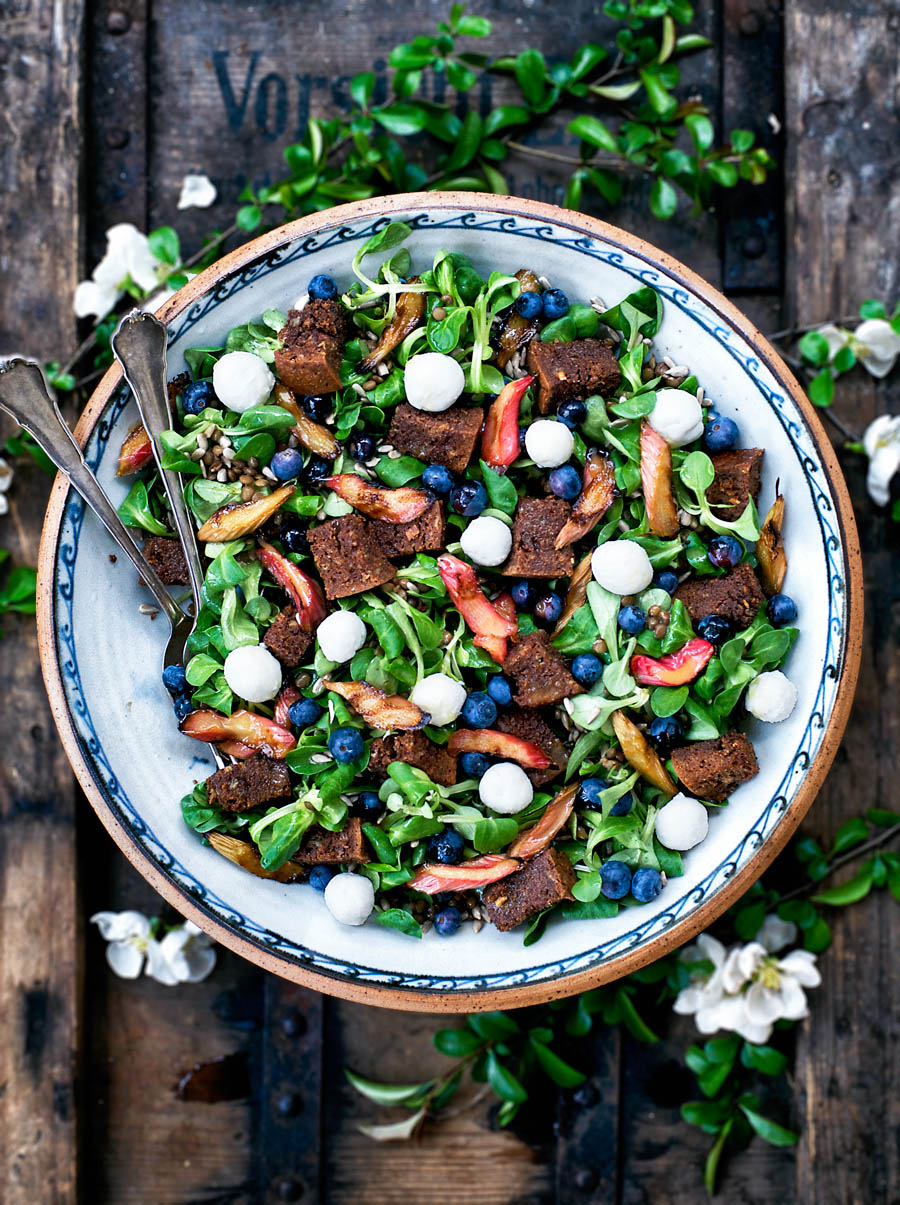A big serving bowl with lamb's lettuce, blueberries, rhubarb, and croutons on a wooden crate.