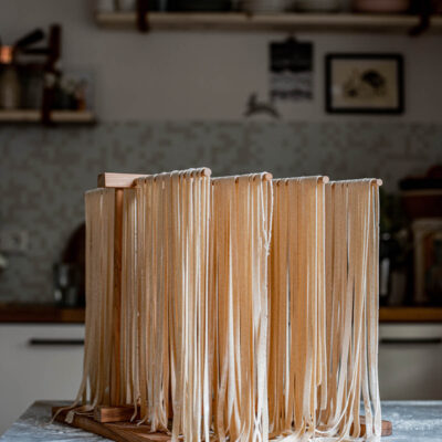 Long fettuccine noodles drying on a wooden pasta drying rack.