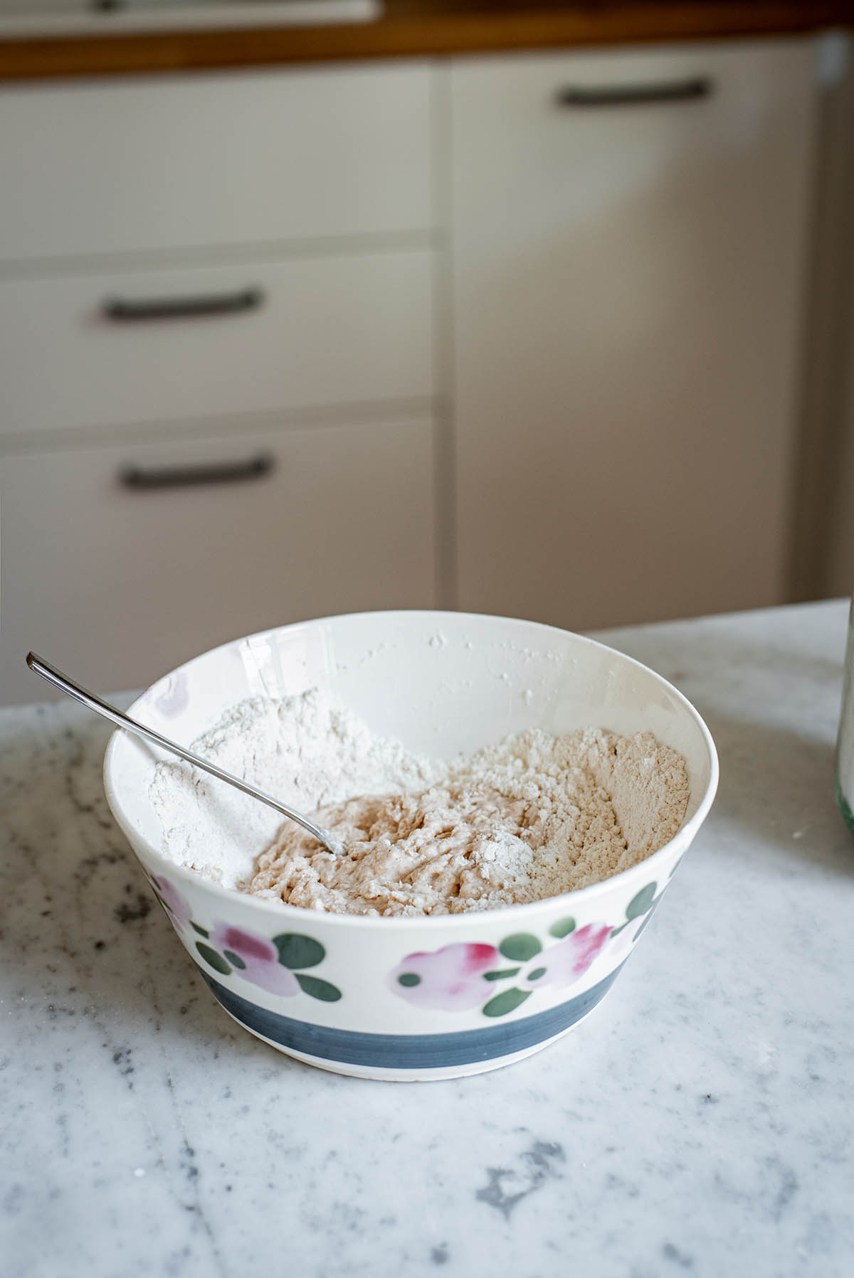 Spelt pasta dough in a bowl with a fork, partially mixed.