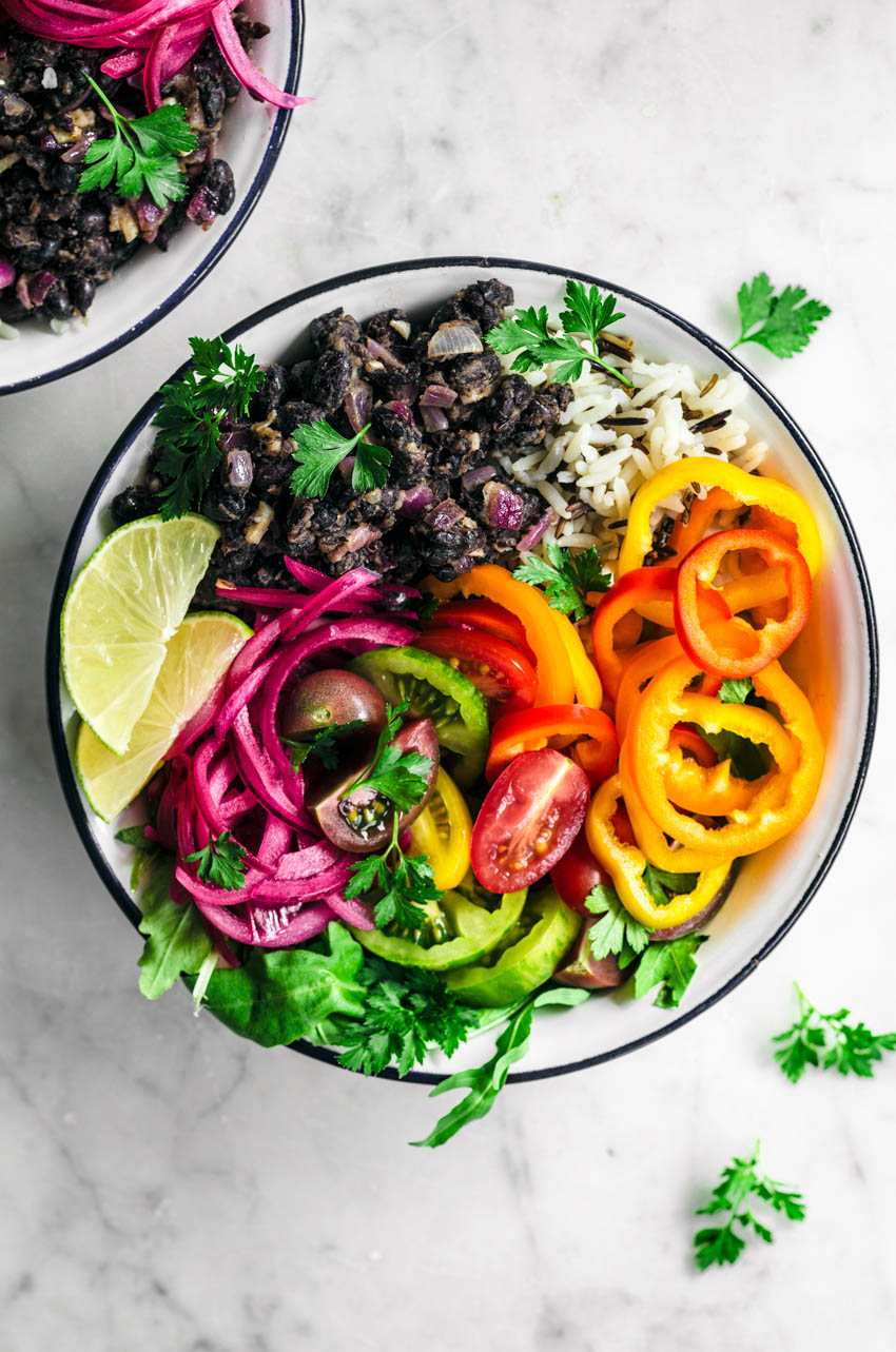 Close up of vegetable burrito bowls with black beans, rice, pickled onions, and summer vegetables.
