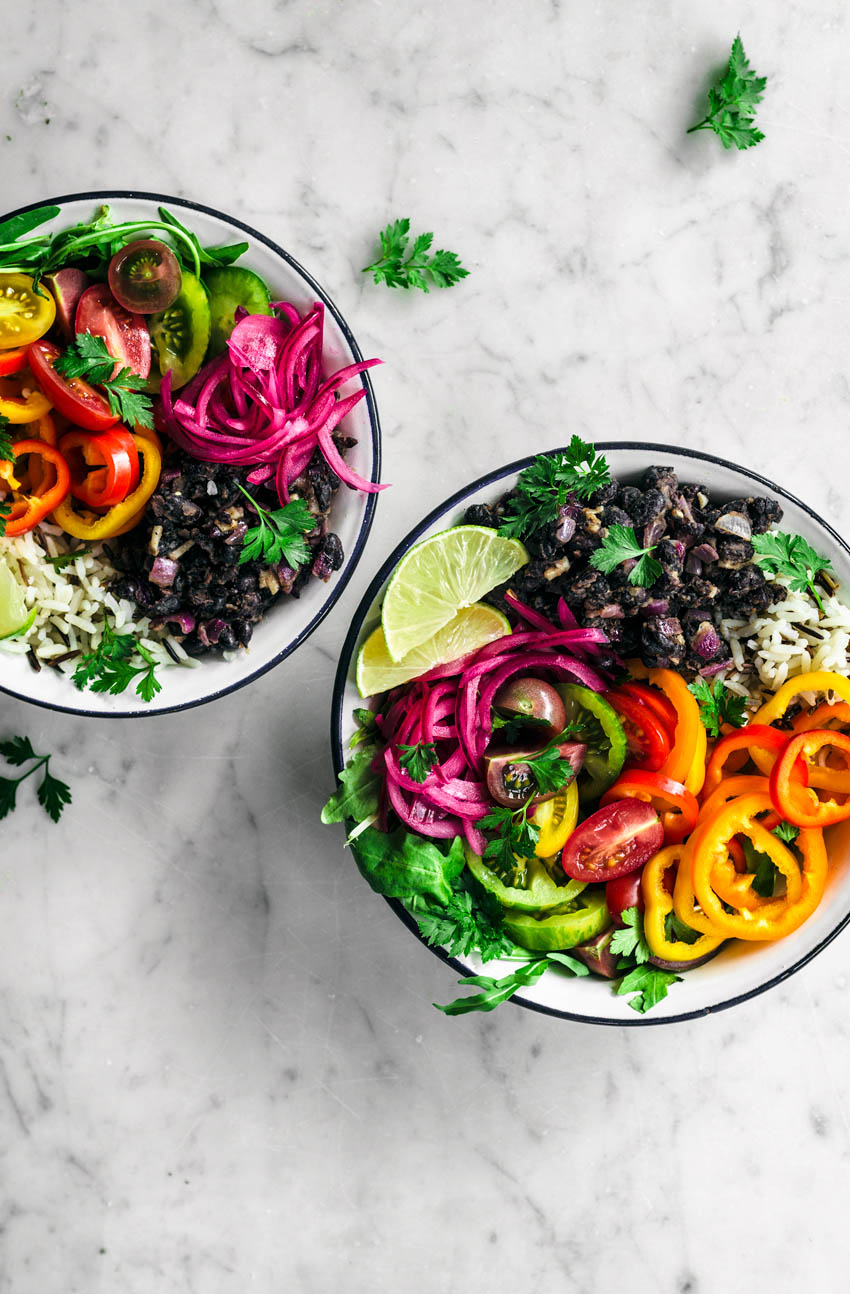 Vegetable burrito bowls with black beans, rice, pickled onions, and summer vegetables, bowls half in shot.
