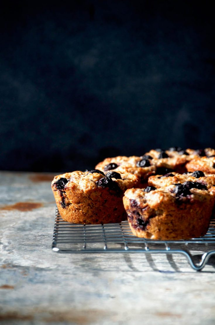Blueberry muffins on a metal cooling rack in front of a dark background.