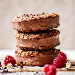 A stack of three oatmeal cookie chocolate ice cream sandwiches, decorated with raspberries and flowers.