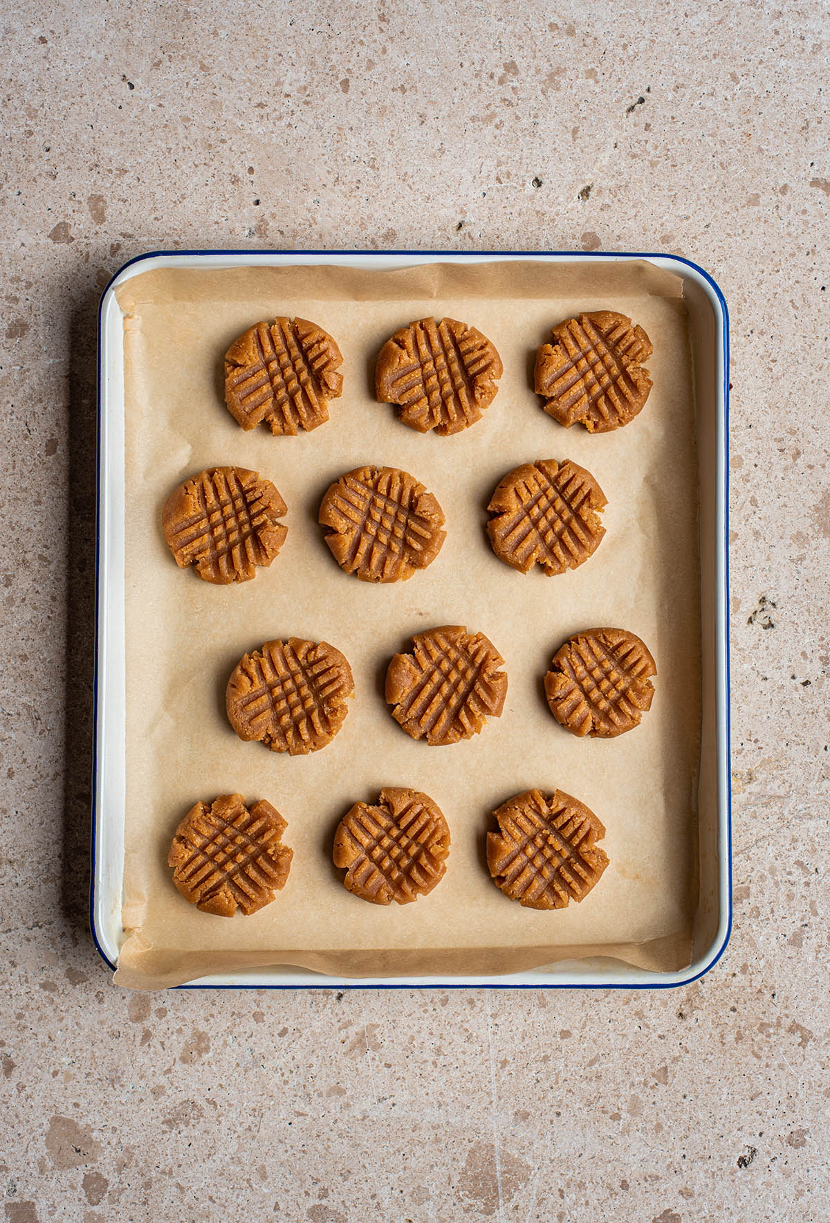 Unbaked cross-hatched peanut butter cookies on a tray, top down view.