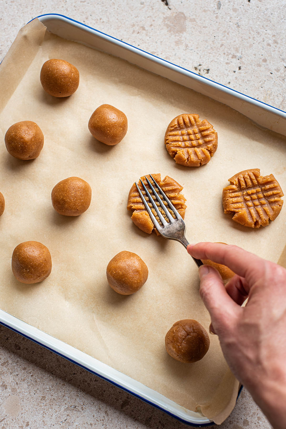 Woman's hand pressing a fork into balls of peanut butter cookie dough.
