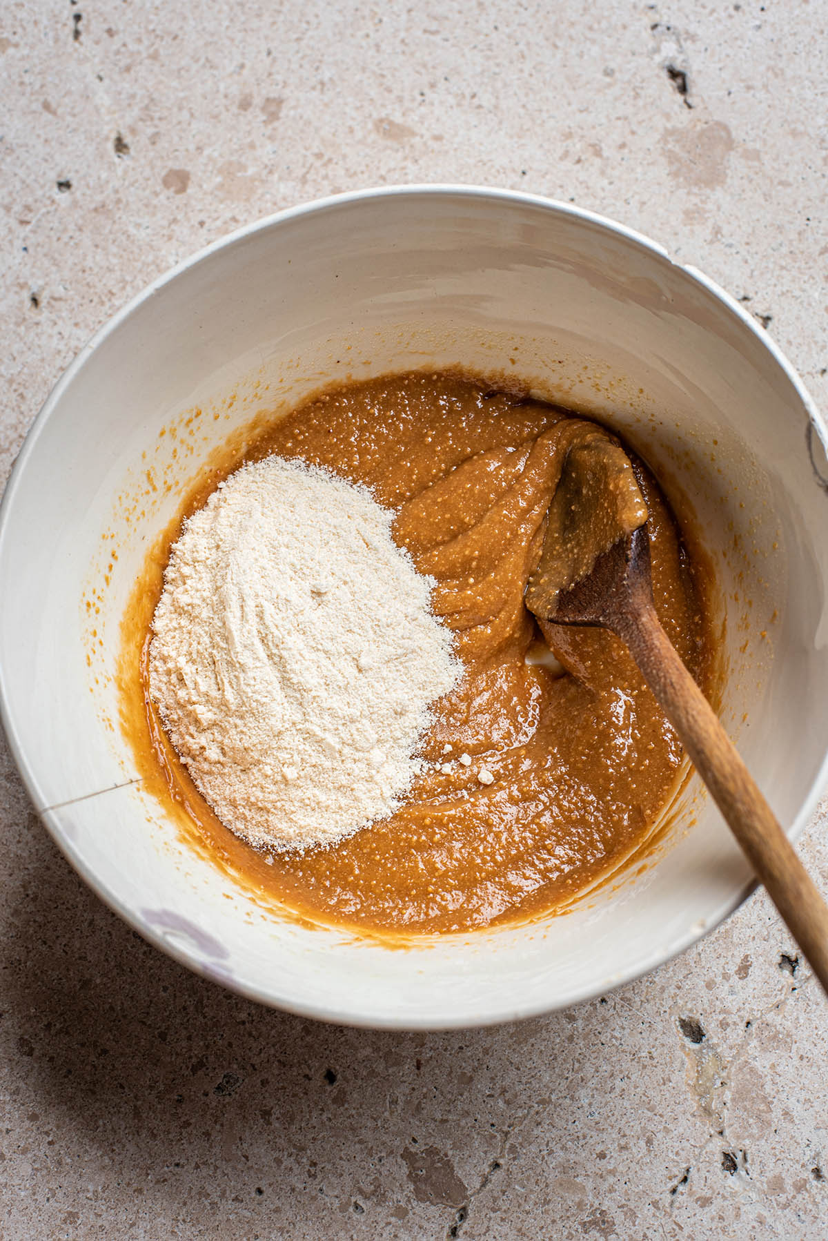 Coconut flour added to peanut butter mixture in a bowl.