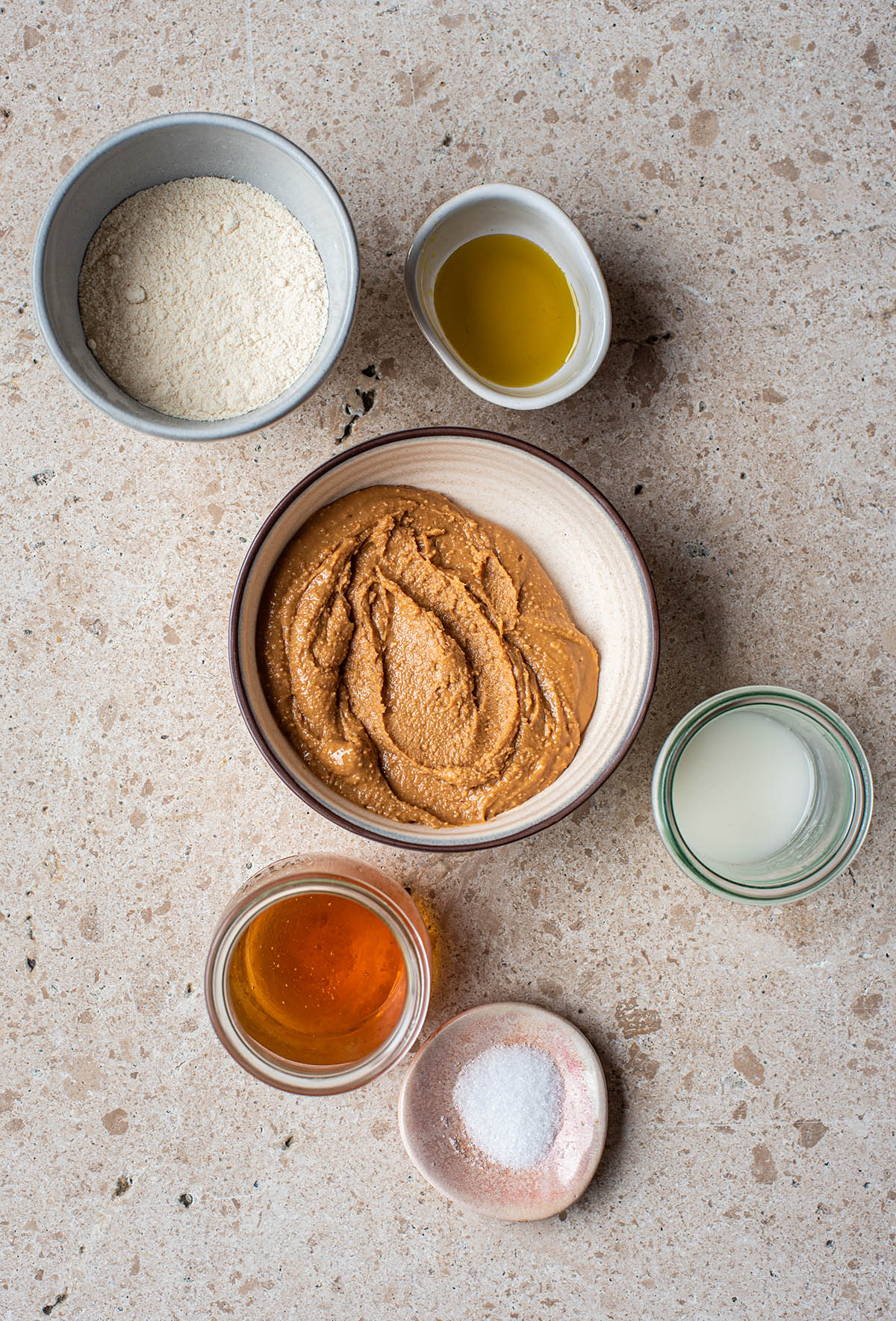 Gluten free peanut butter cookie ingredients: coconut flour, olive oil, unsweetened peanut butter, milk, maple syrup, and salt.
