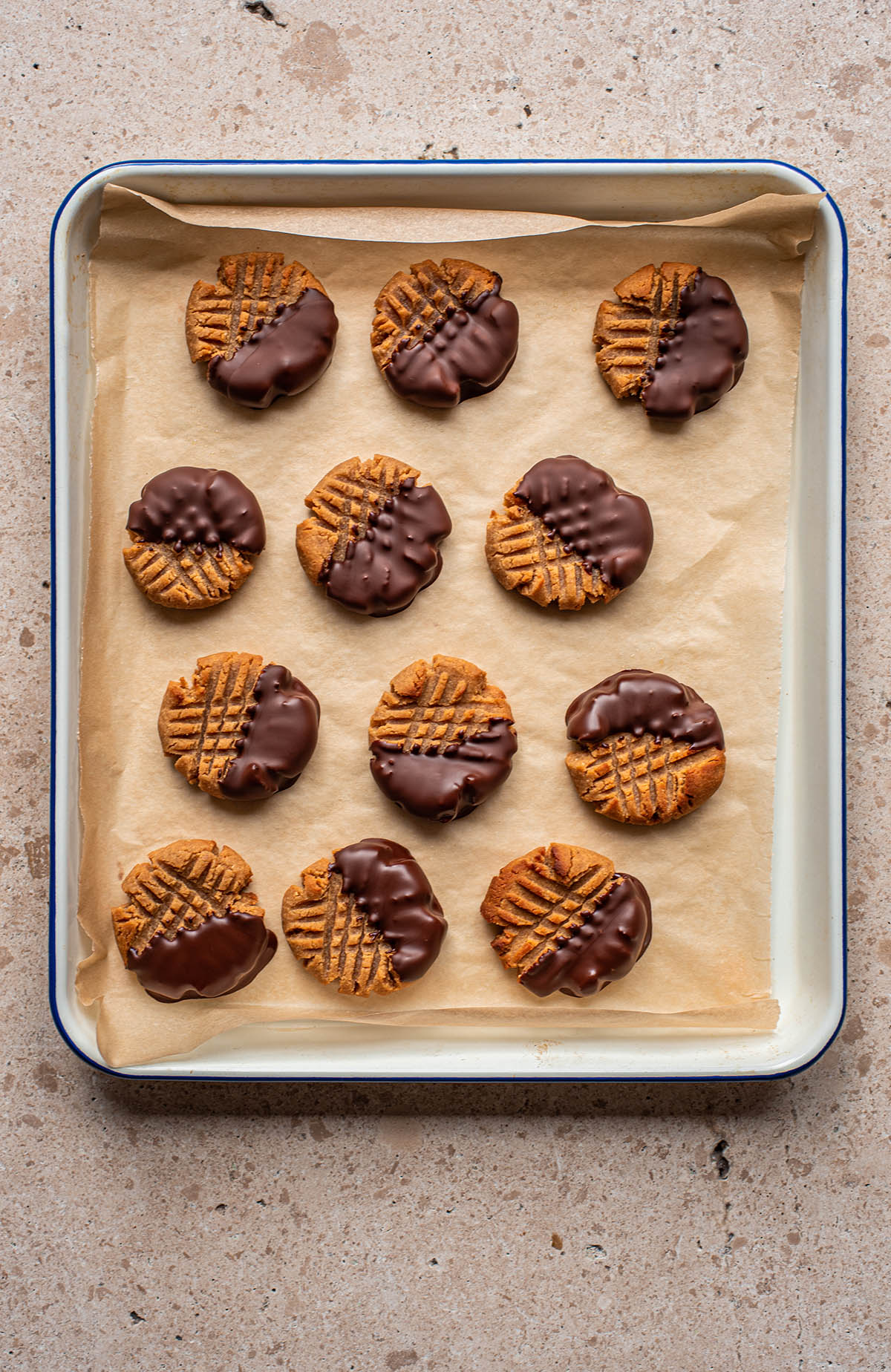 Chocolate dipped peanut butter cookies on a tray, top down view.