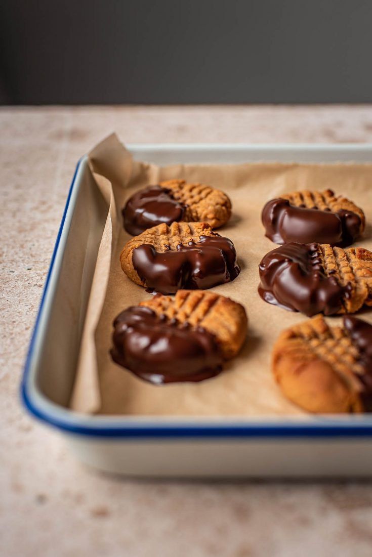 Chocolate dipped peanut butter cookies on a tray.