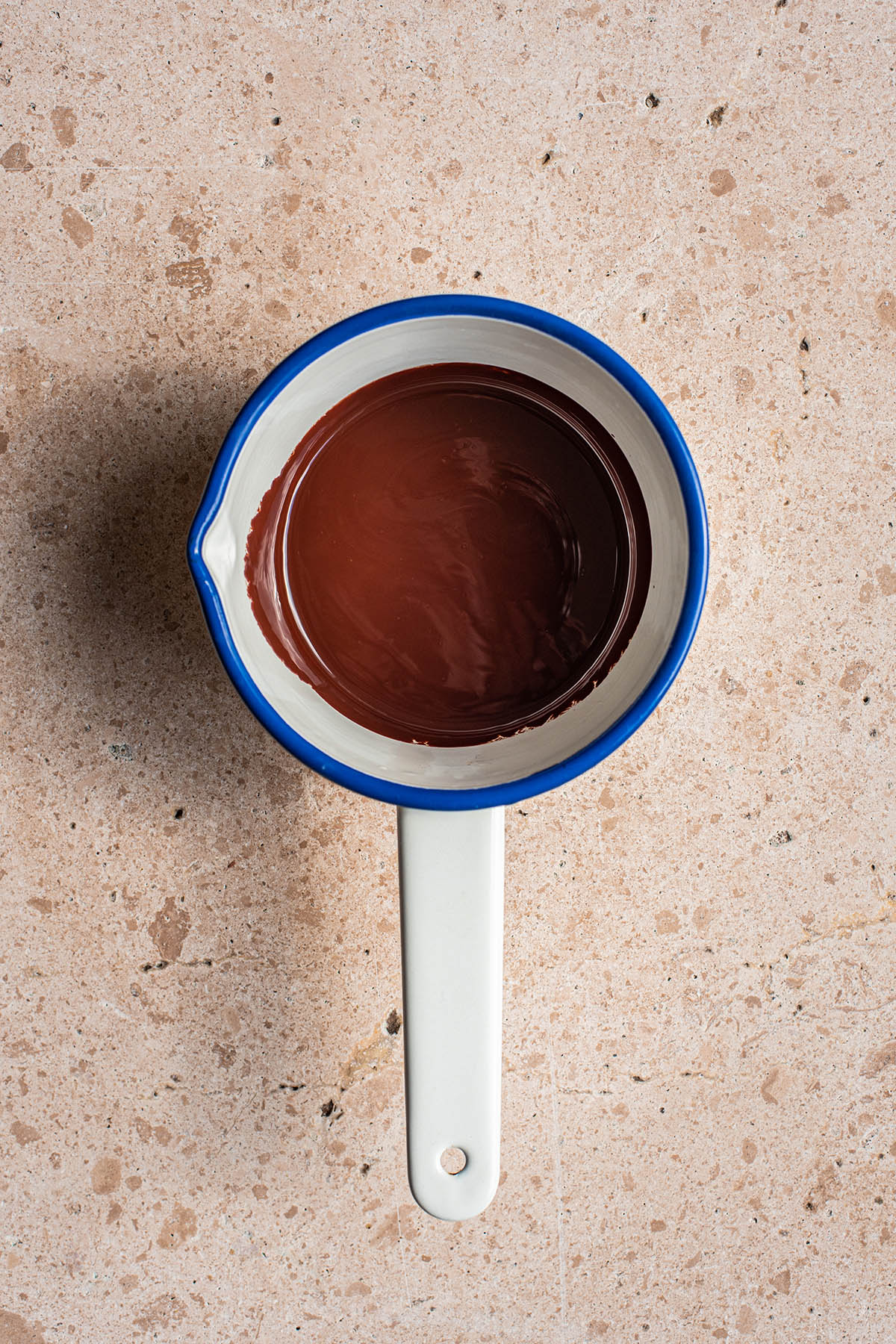 Small enamel saucepan filled with melted chocolate.