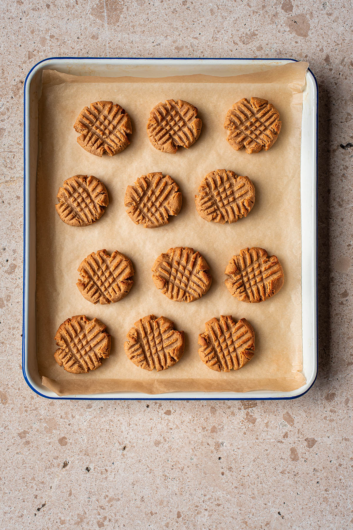 Baked cross-hatch gluten free peanut butter cookies on a tray, top down view.