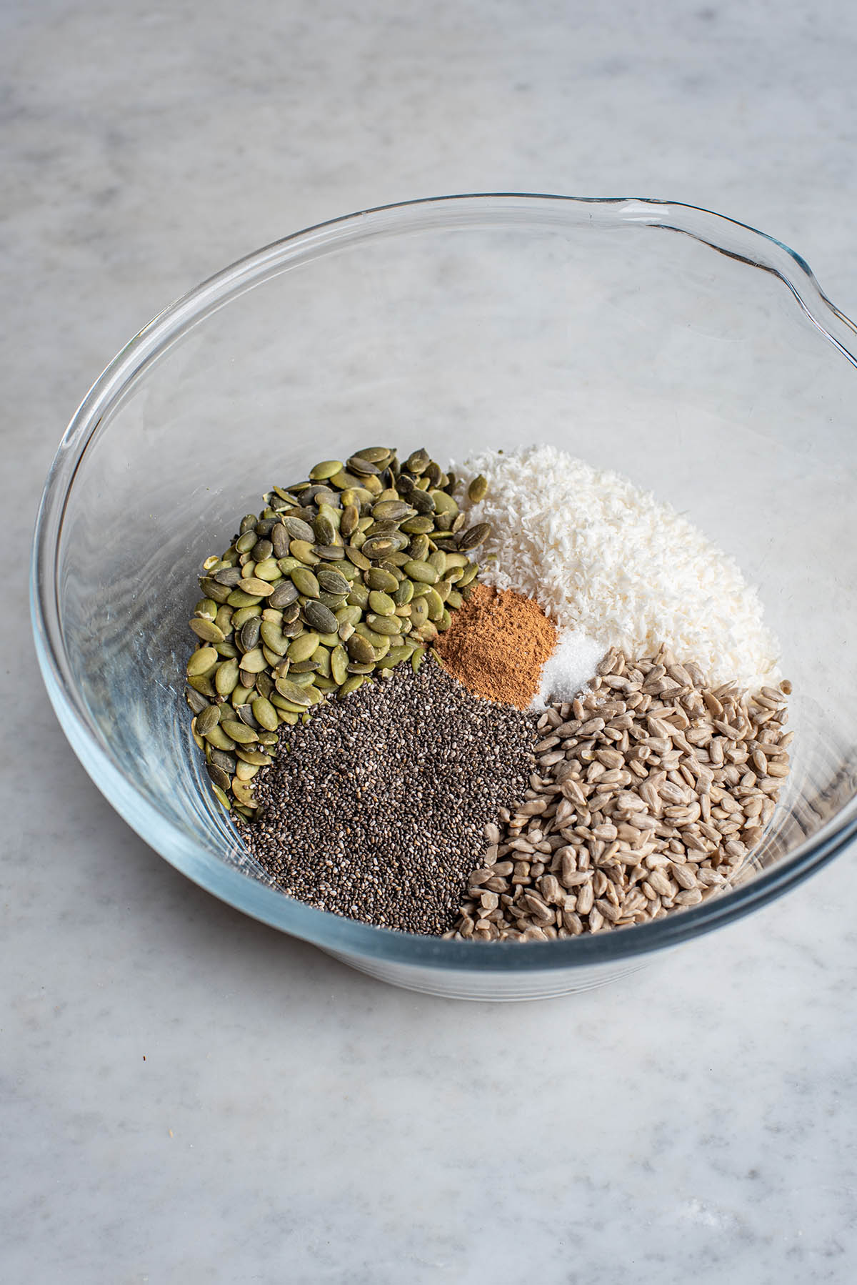 Dry ingredients for granola in a large glass bowl.