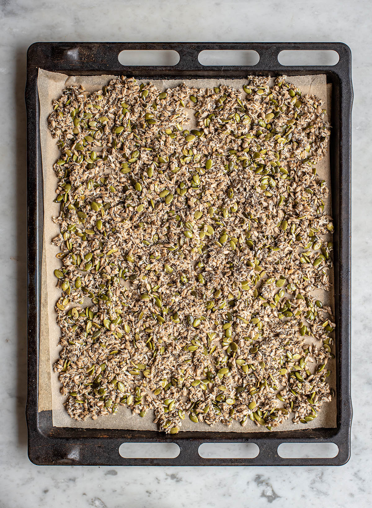 Granola on a large sheet pan, unbaked.