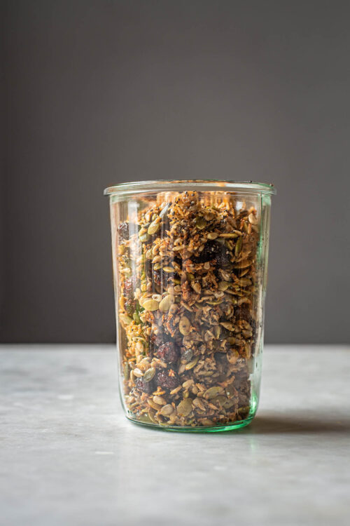 Grain free granola with dried cranberries in a jar, front view.