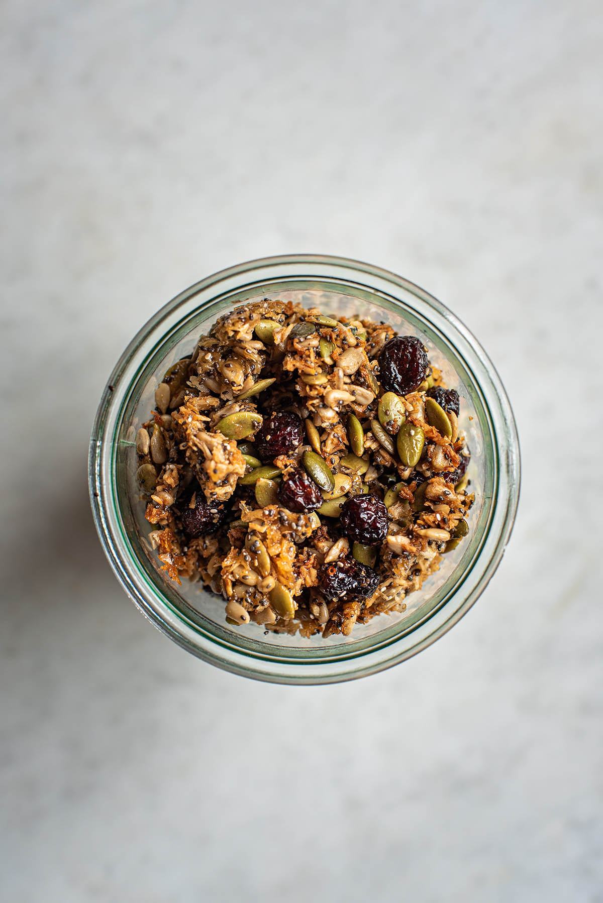 Grain free granola with dried cranberries in a jar, top down view.