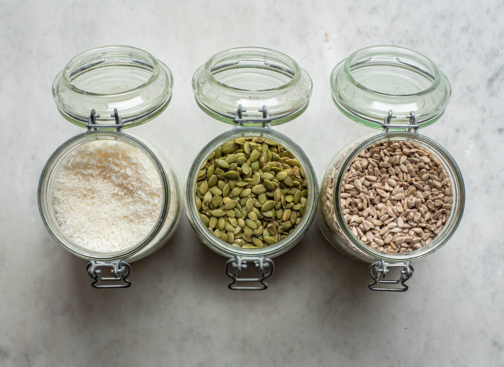 Three flip-top glass jars in a row, filled with coconut, pepitas, and sunflower seeds.