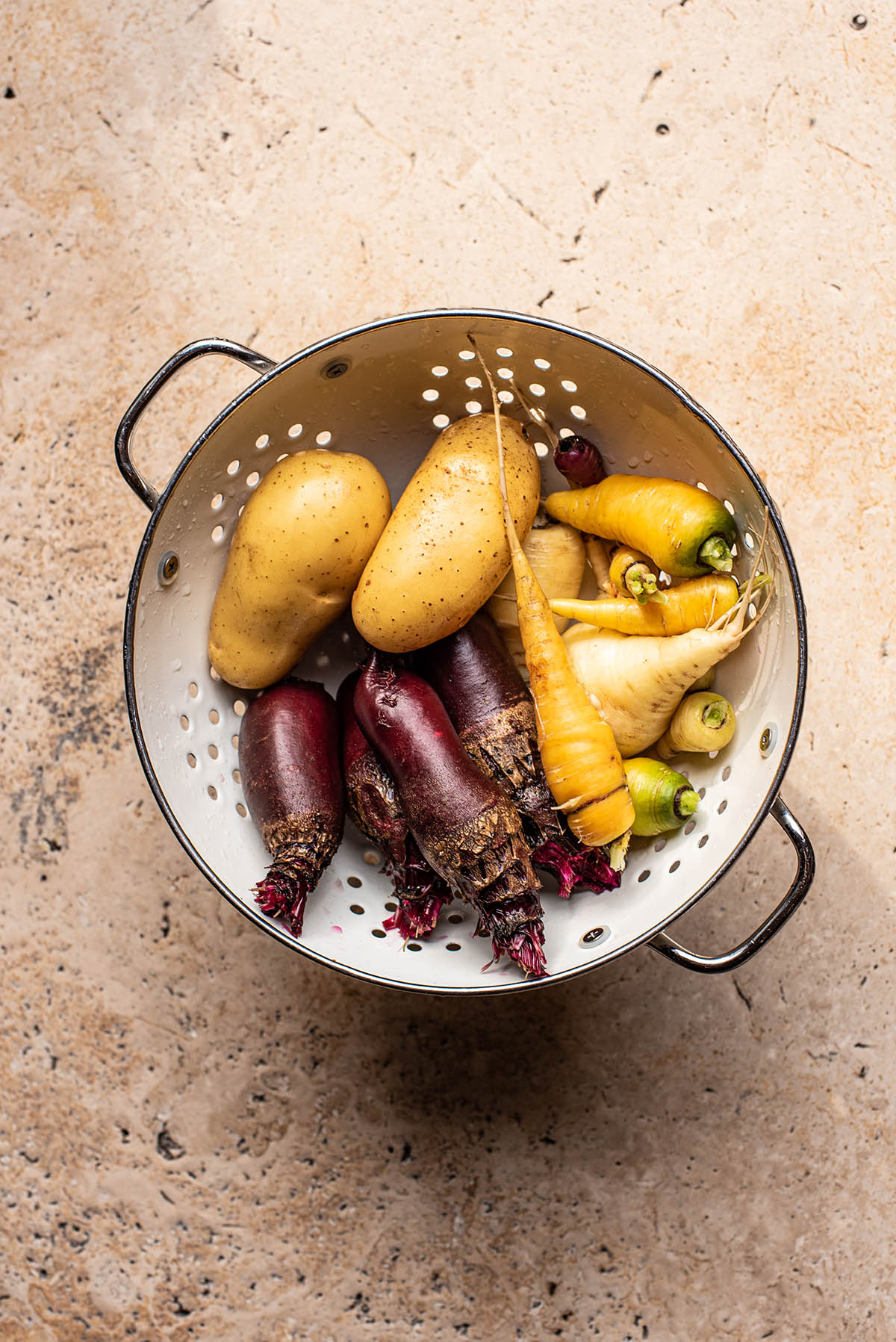 Potatoes, beets, and carrots in a large colander.