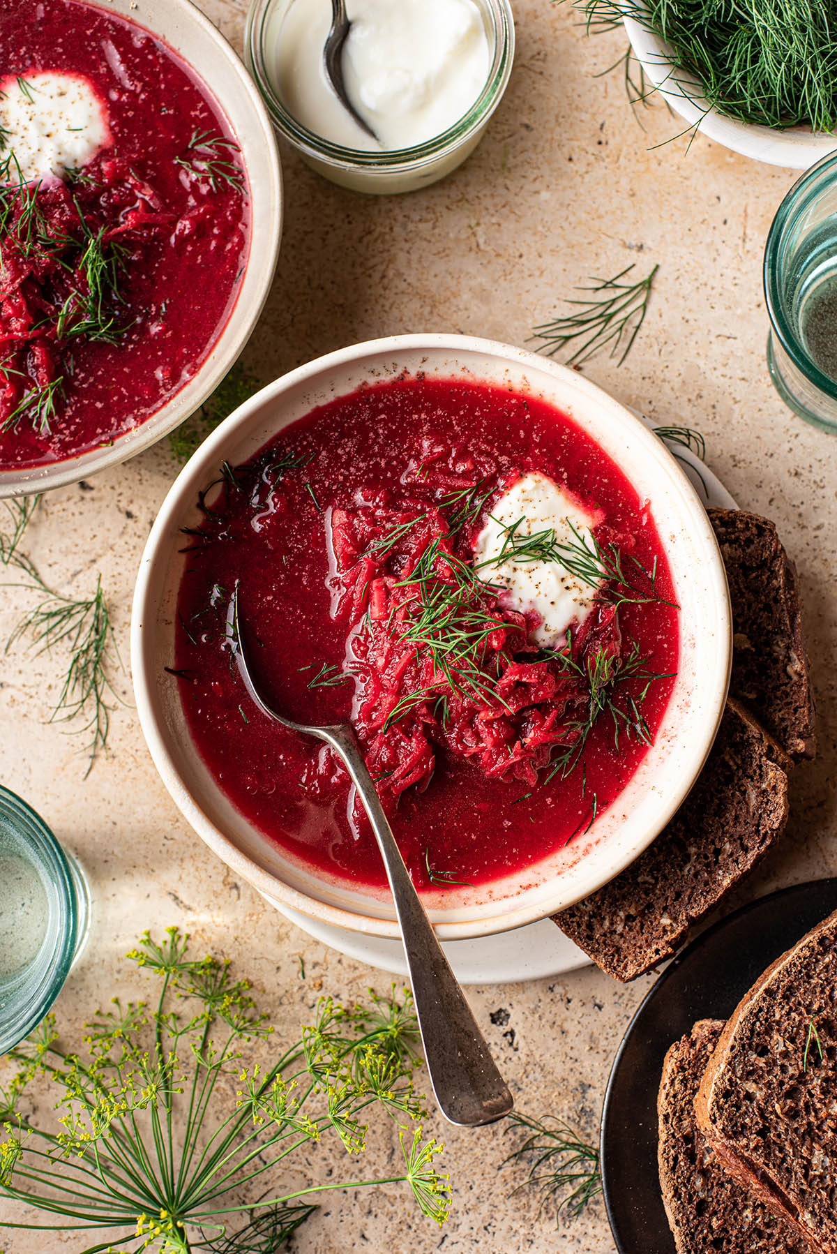 Two bowls of borscht topped with yogurt and dill.