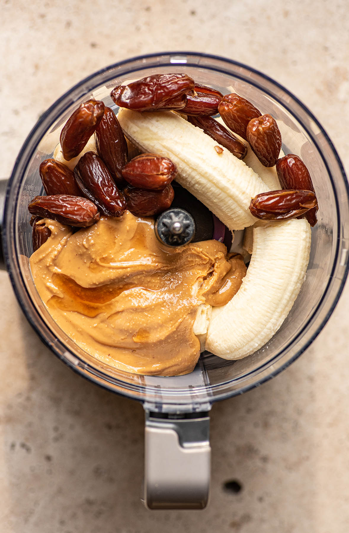 Peanut butter, bananas, dates, and vanilla in a food processor.