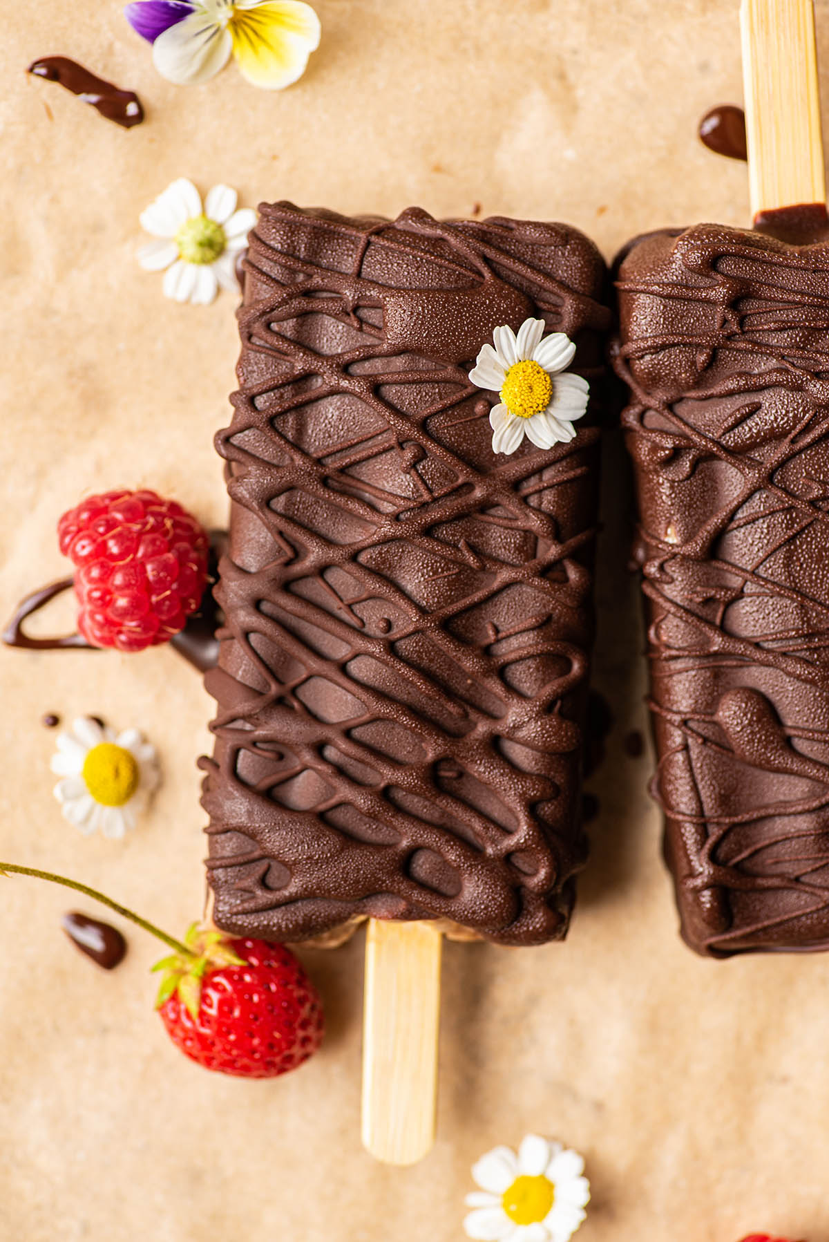 Dark chocolate coated popsicles on parchment paper with flowers and berries.